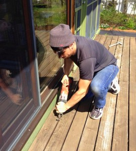 "Carpenter Mike Roldan cuts the through nails on Deck House Balcony here using a sawzall a grinder with a metal cutting wheel is also convenient for this task. The decks on these houses are constructed of 3x6"" solid cedar timbers. They are fastened to each other with long nails through the sides of the boards and span eight feet without intermediate support on the finished decks. The deck surfaces on a Deck House which has been built to specification perform greater structural work than on a conventional stick framed deck.  Their removal should be conducted with care to avoid injury or damage."